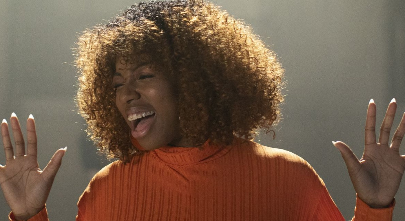 A black woman sings. her head is turned to the right, eyes closed and wears an orange top