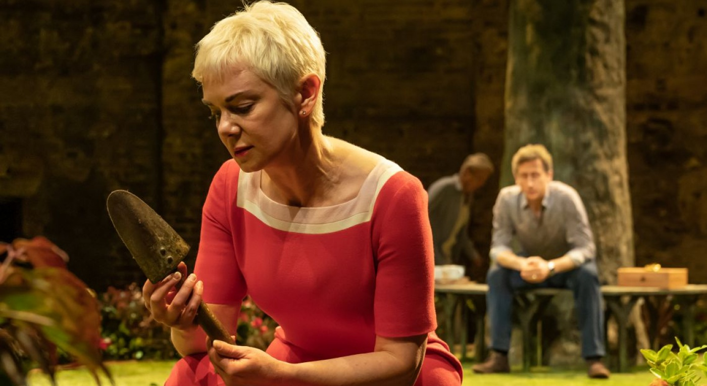 Albion at the Almeida. Victoria Hamilton (Audrey). Photo credit Marc Brenner. A woman in a red dress kneels on the ground. A man sits on a bench in the background.