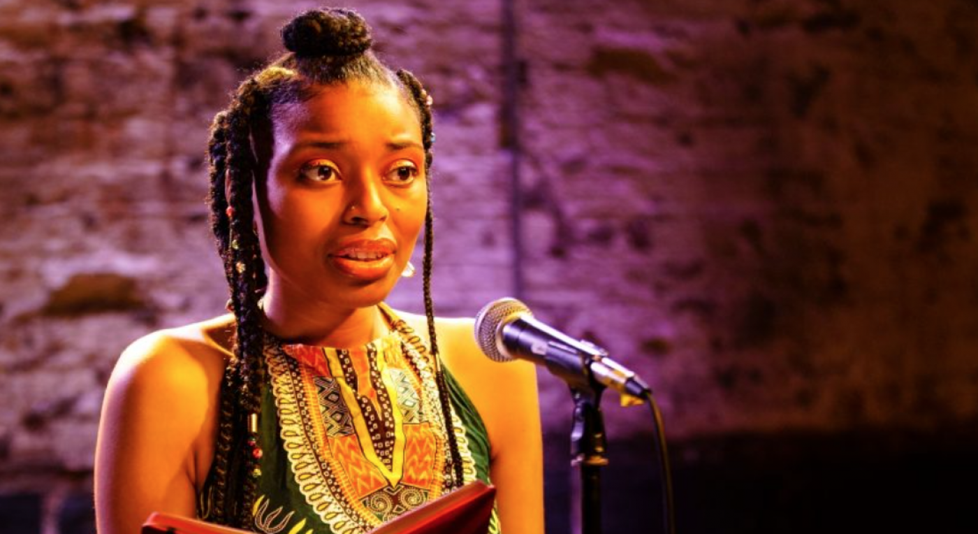 A young black woman with braids stands on stage in front of a microphone. She holds an open book in front of her.
