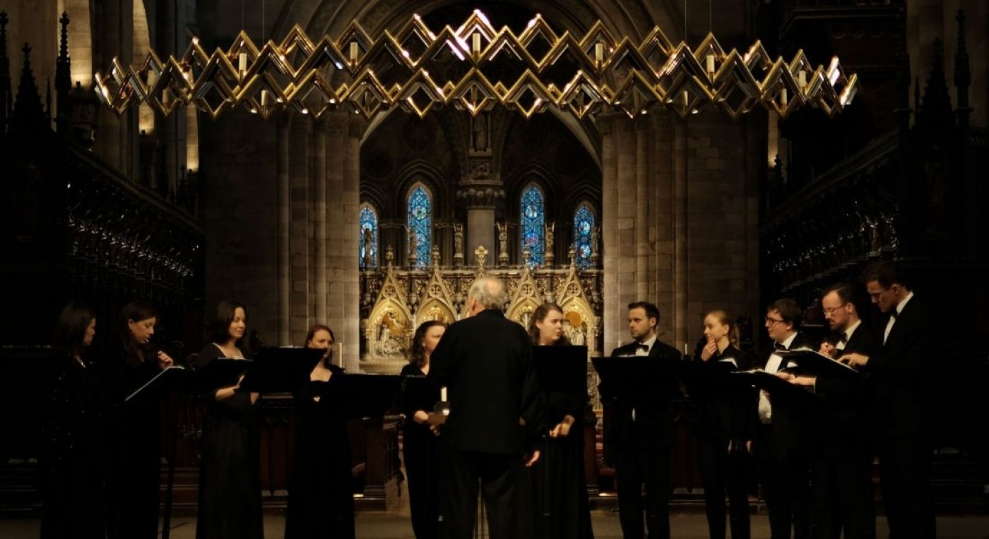 Choir wearing black perform in a cathedral. They perform by candlelight