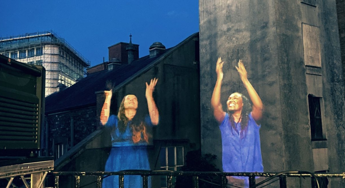 2 women are projected onto Bristol buildings. They use sign language to communicate