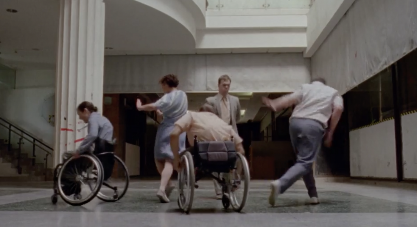 Artificial Things StopGap Dance features 5 dancers on stage. Two dancers are in wheelchairs. They are dancing in a disused shopping mall