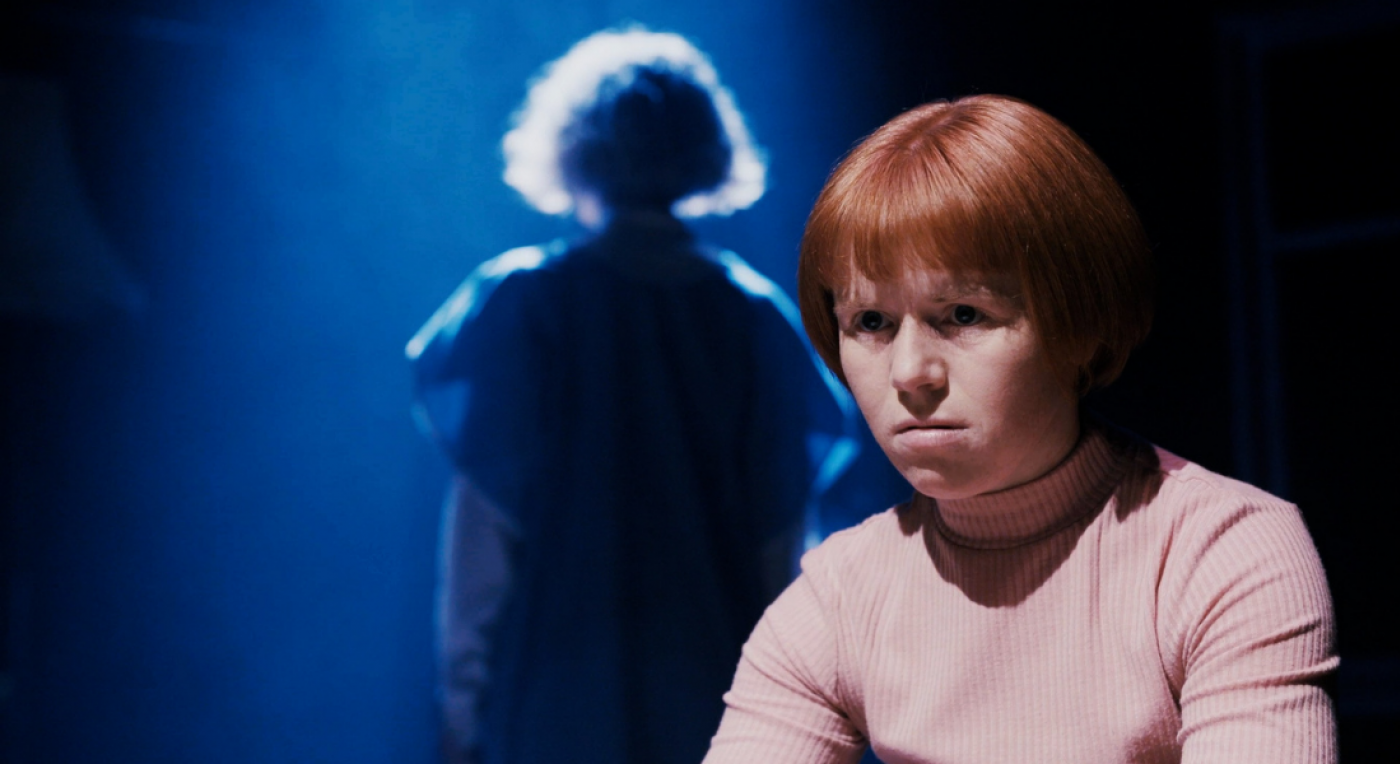 A young woman with red hair stares into the distance. She wears a pink polo neck. A shadowy figure is in the background