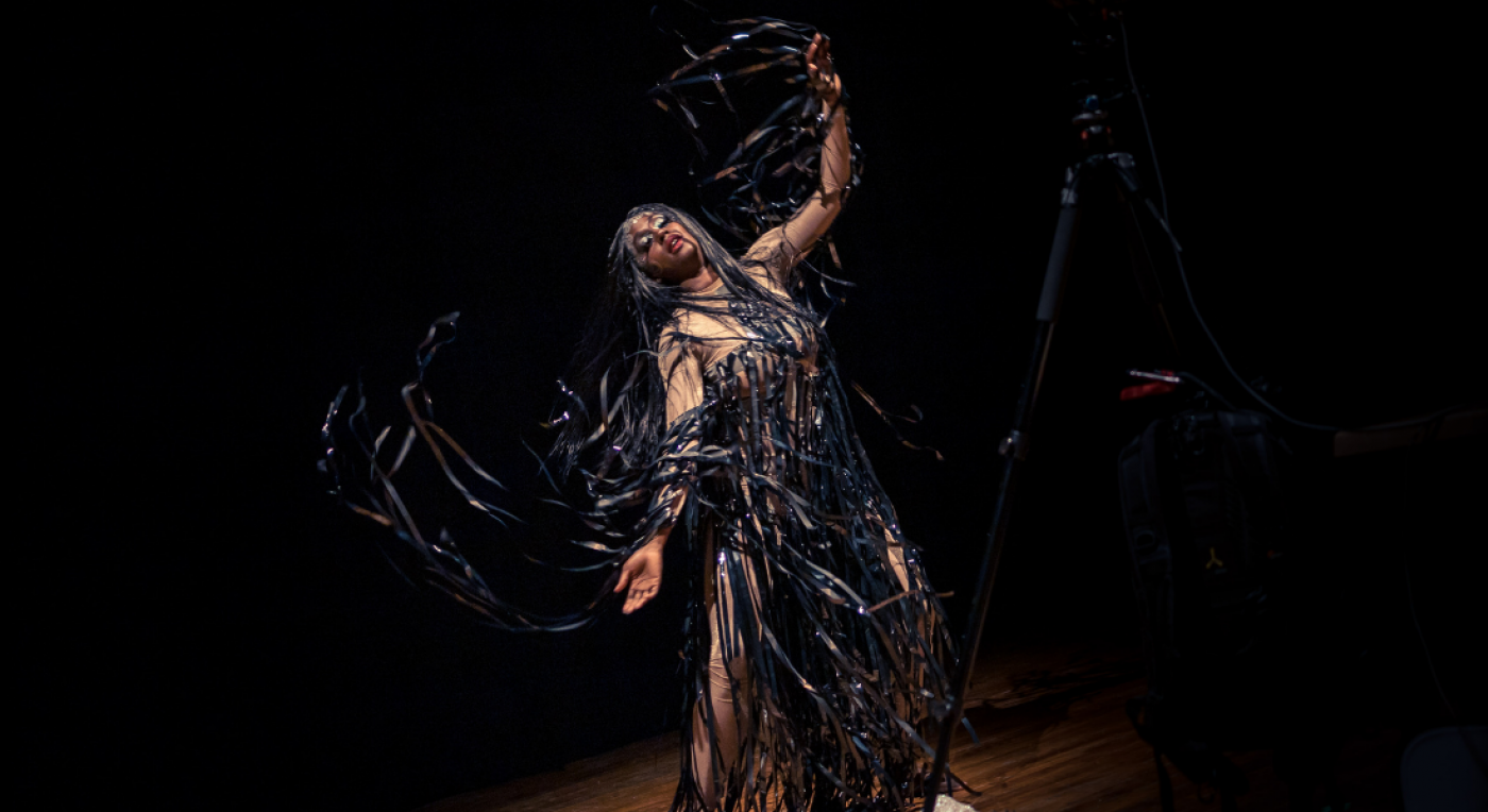 A black woman wears an intricate costume. She dances alone under a spotlight. Her eyes are closed