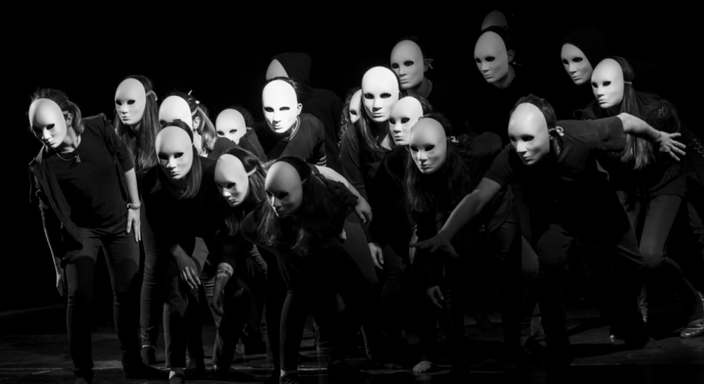 Theatre production, with a group of people in masks dancing on a black background