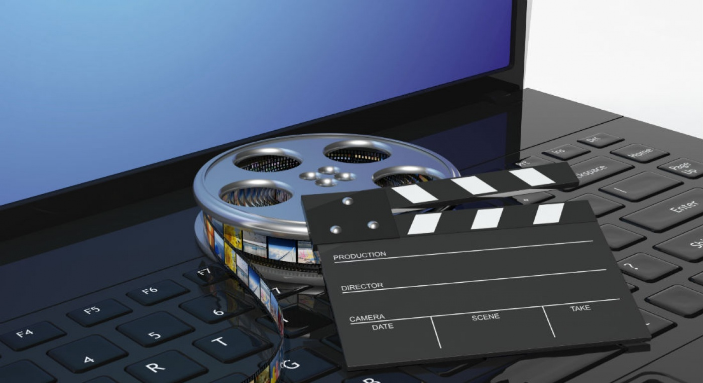 Film clapper and movie reel with digital imprints on a laptop keyboard