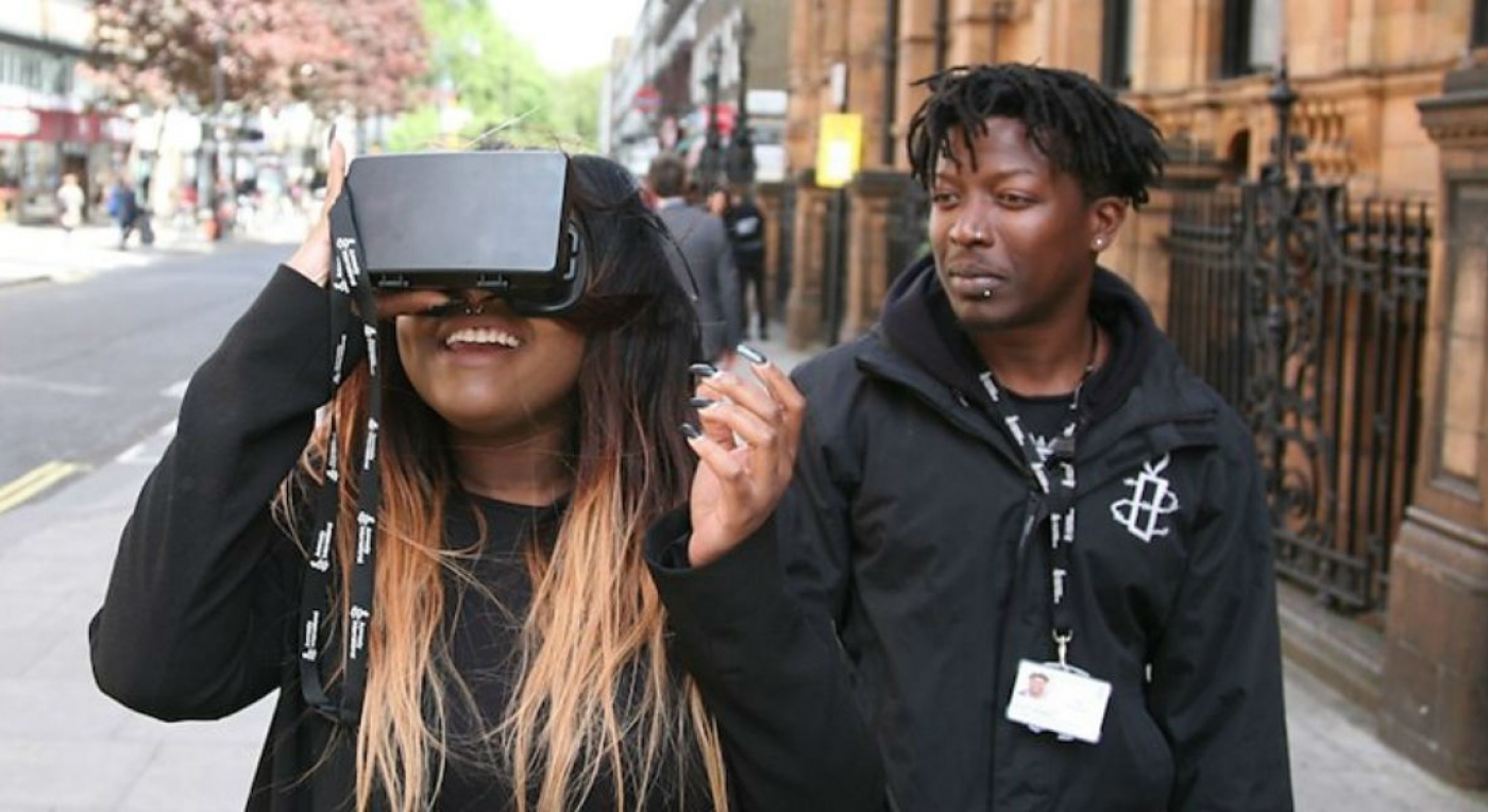 Woman using VR headset with man looking on