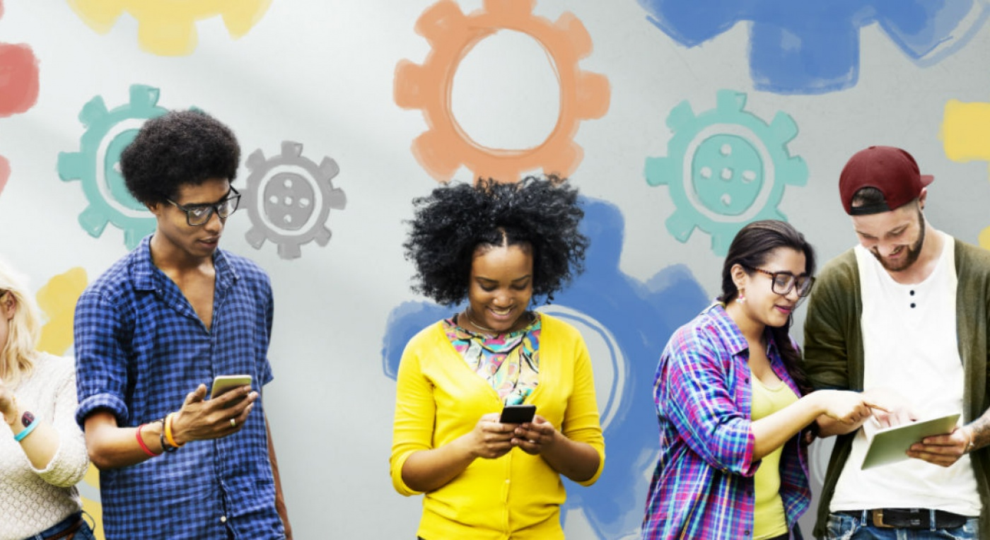 Group of people on smartphones and tablets in front of a background with colourful gears