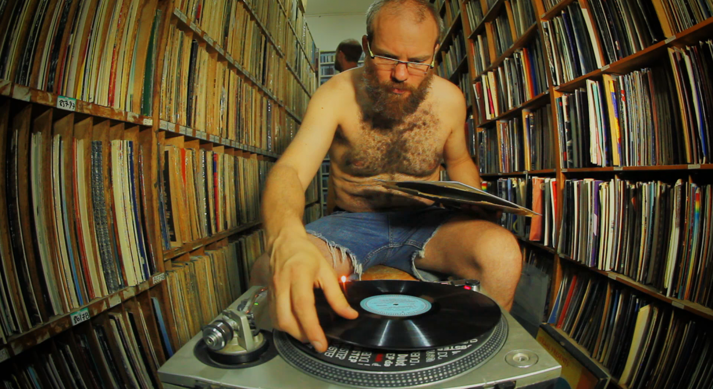 Shirtless man with a record player in a vinyl library