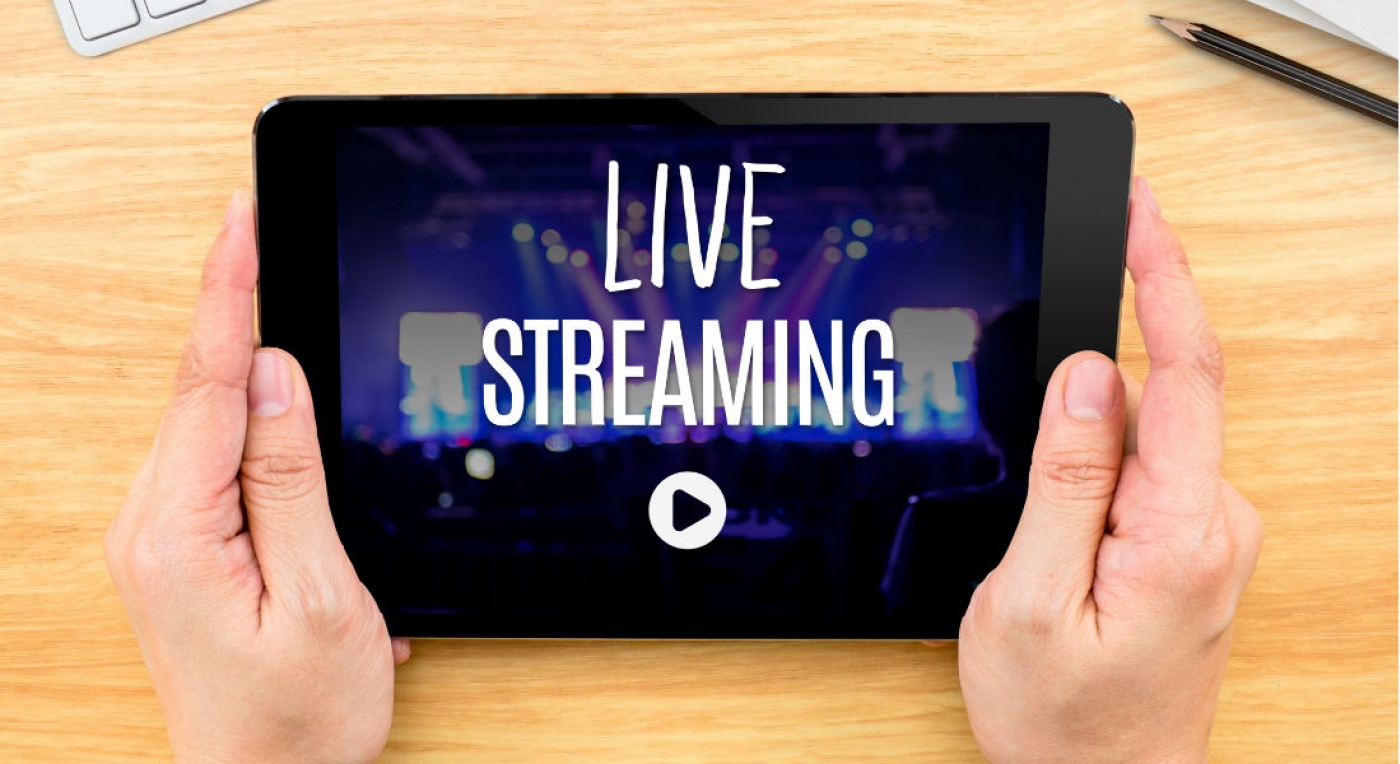 words live streaming on tablet, on wooden desk background, being held