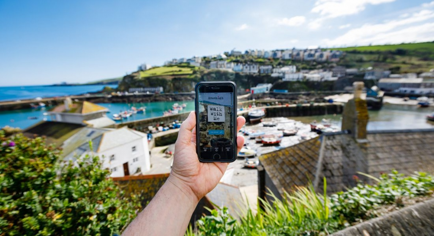 Walk with Me app. Image shows a mobile phone looking over Cornish coastline featuring seaside town Mevagissey