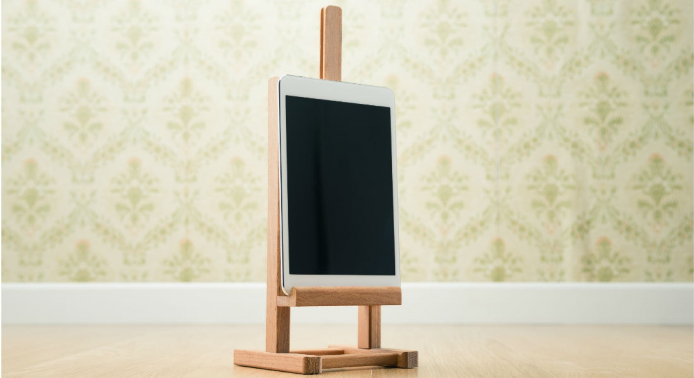 Digital table on a wooden easel against a floral wallpaper background