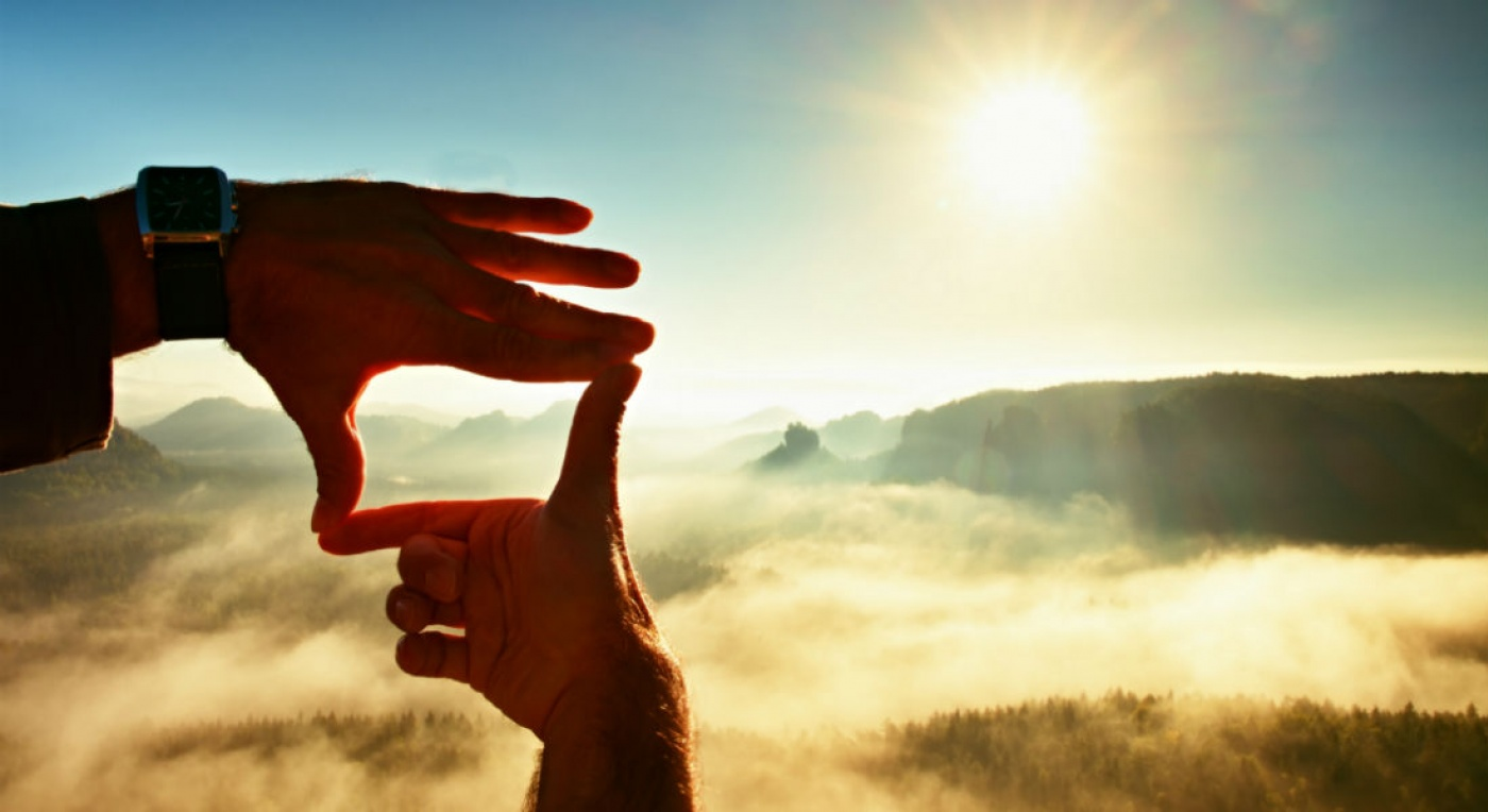 Hands in shape of a frame, overlooking sunset on mountain background