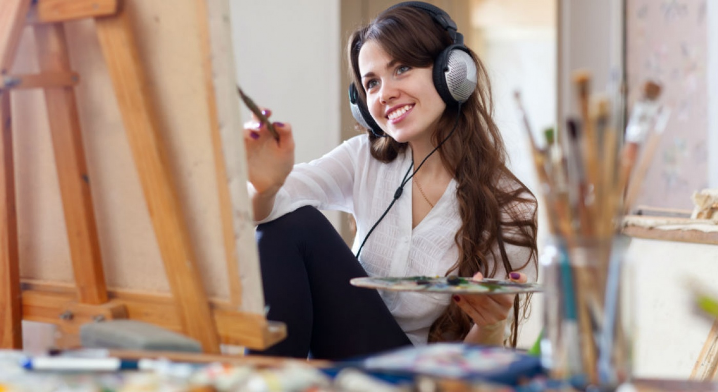 Lady listening to music on headphones whilst painting with oil paints on a canvas