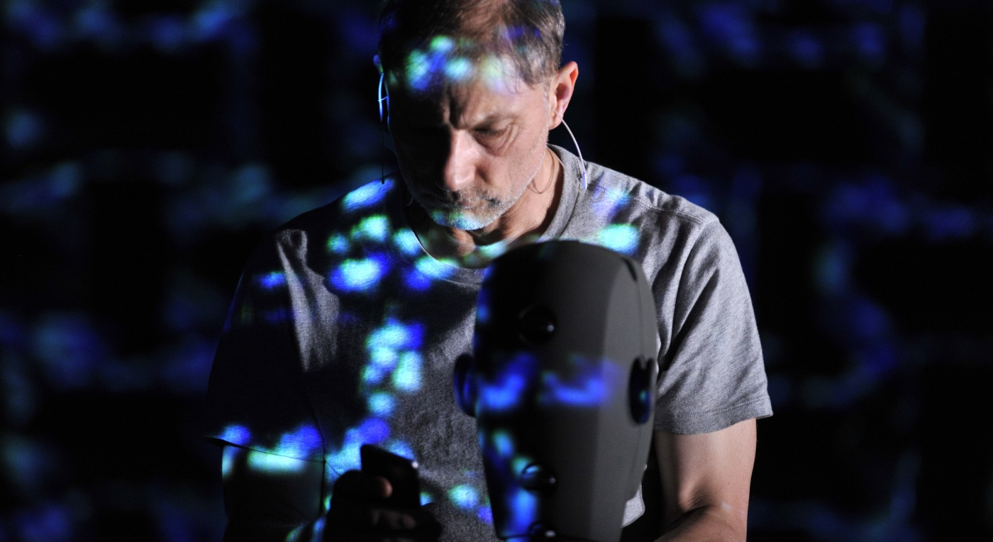 Actor Simon McBurney appears on a dark stage wearing a grey t-shirt. He is dappled in blue light. It is for a performance of The Encounter Credit: Robbie Jack Robbie Jack setting up The Encounter
