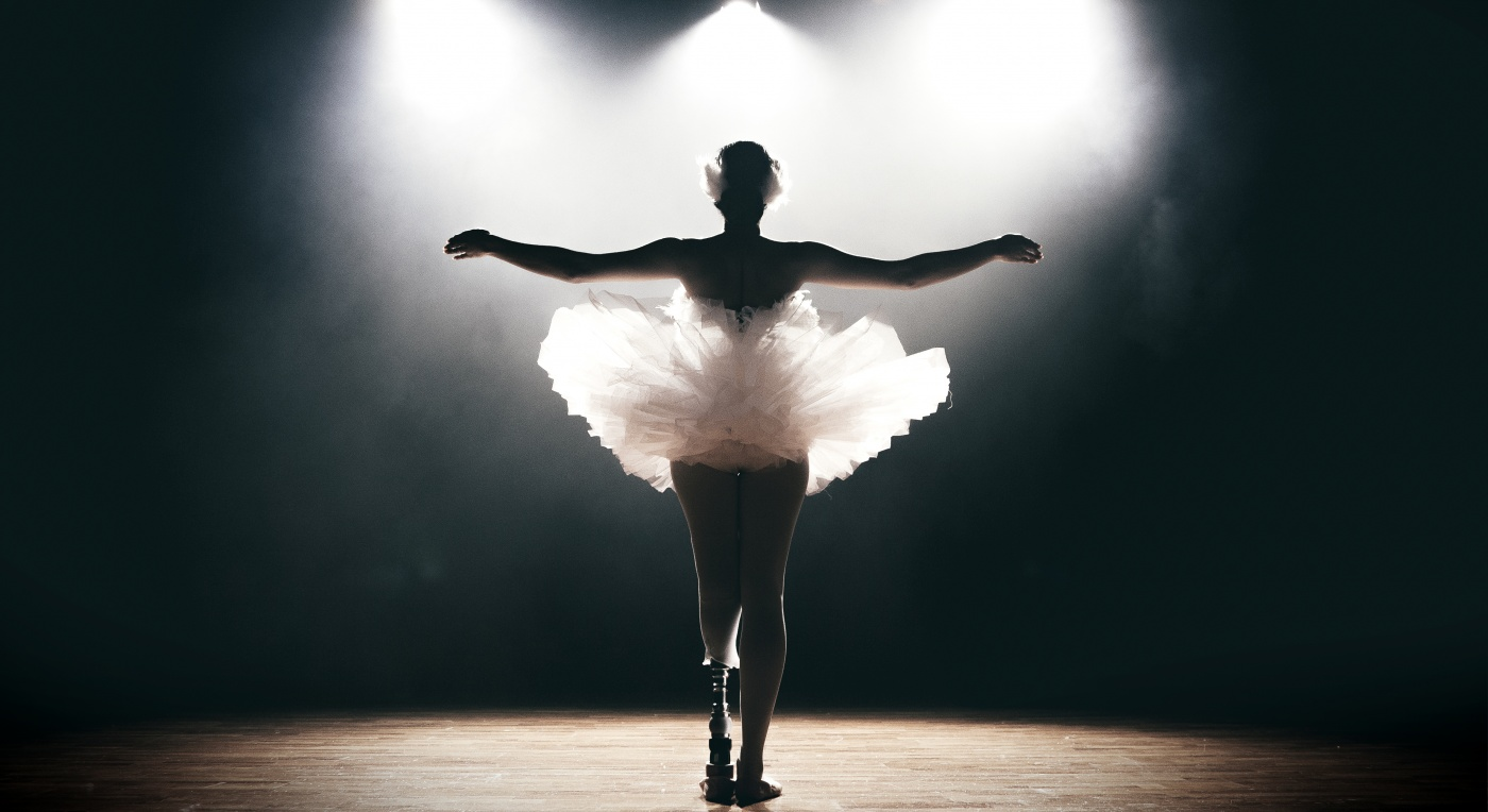 A dancer in a white tutu is bathed in light on a stage. Her arms are outstretched and she has a prosthetic leg