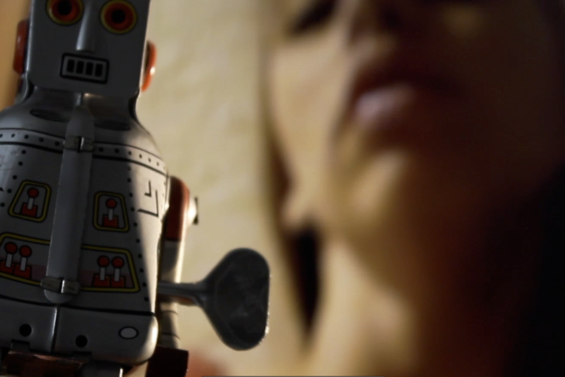 A composite still from a film that shows a wind up toy robot in the front left of the frame and a soft focus cropped head shot of a woman in the back right