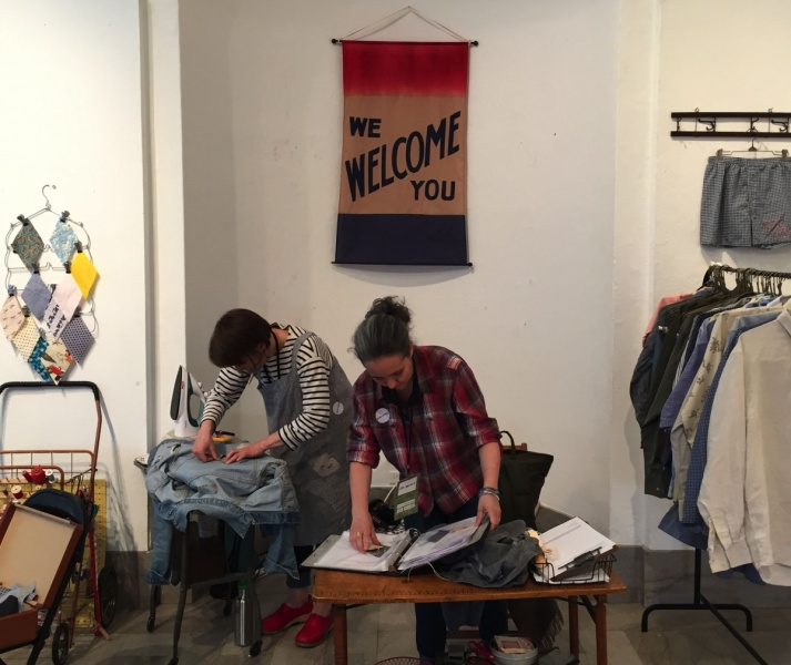 Two Itinerant Quilters inserting pieces of fabric into a denim jacket