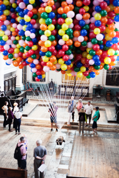 Thousands of brightly coloured helium filled party balloons lift the artists trussed and tied body off the ground. Audience members are walking around the installation which is set in a church