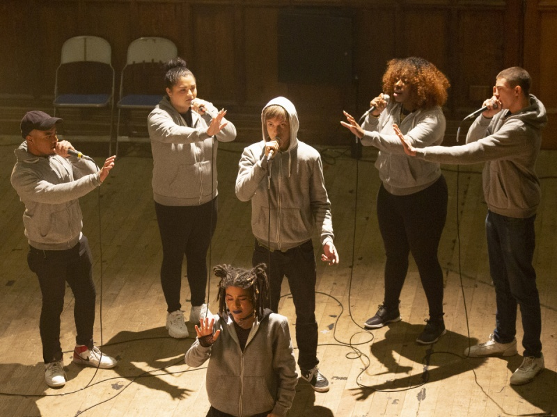 six young people stand in a semi-circle sining into microphones. They wear black trousers and greay hoodies