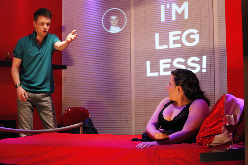 A red stage set with two actors: a male stands, arm raised in animated conversation with a woman, who is on a bed dressed in black lace. She has no legs and on the wall behind her the text 'I'm legless' is projected like a text message.