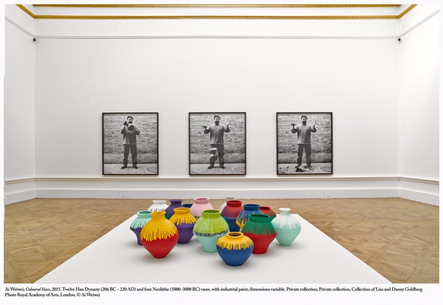 "Exhibit titled ""Coloured Vases"" featuring twelve Han Dynasty (206 BC – 220 AD) and four Neolithic (5000–3000 BC) vases that have been dipped in bright coloured industrial paint. Behind is a series of 3 photographs showing Ai Wei Wei dropping a vase."