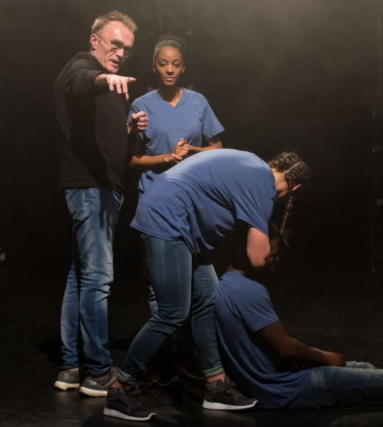 Danny Boyle pointing towards the camera, directing 3 members of Boy Blue Entertainment; One standing, once crouched and one sitting on the floor