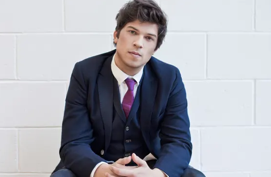 Corey Baker, a young white male choreographer with short brown hair. He wears a blue suit and a purple tie