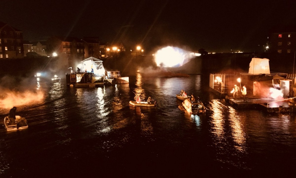 Boats and theatre sets in the Hull Docks at night. Lights illuminate smoke while actors perform on a number of floating sets and small boats as part of Flood live