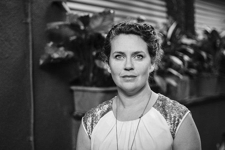 A black and white image of a young white woman. She has curly hair tied up and wears a short sleeved top. Emma Callender, Theatre Uncut