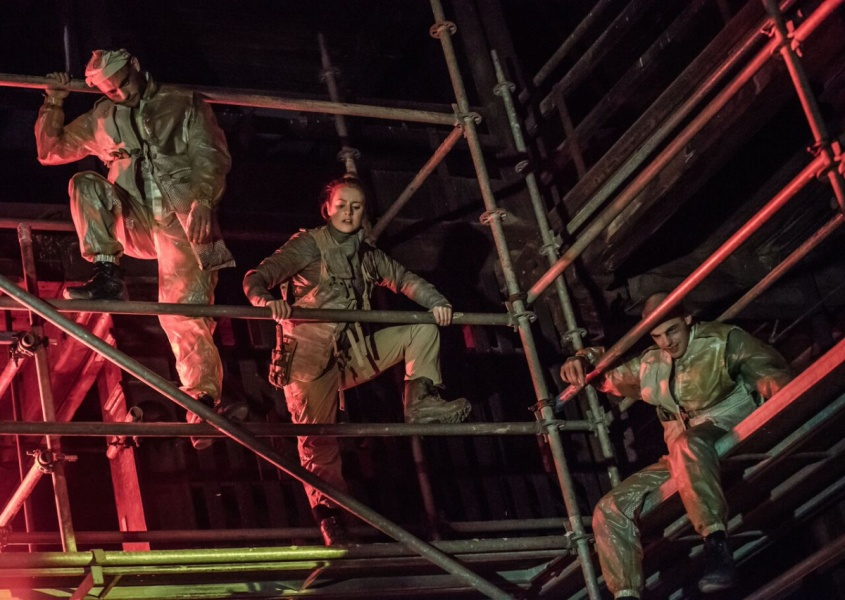 The young people in khaki clothing climbing scaffolding and looking down at something bellow