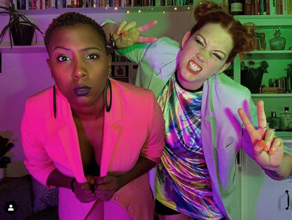 Jade Anouka and Grace Savage. The two women look at the camera, photographed from the waist up. Jade (a black woman) wears a bright pink jacket. Grace (a white woman) stands slightly behind Jade and grimaces holding fingers in a 'victory' sign