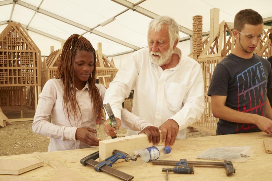 Burn artist David Best and two young people working on the construction of the burn model. Hammering a nail into a block of wood