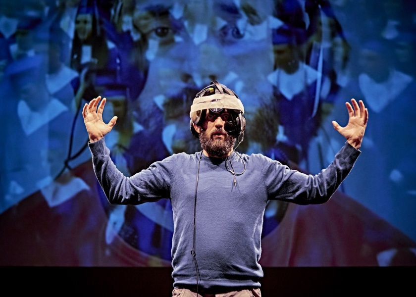 A man stands on stage with his arms aloft. He wears a contraption on his head