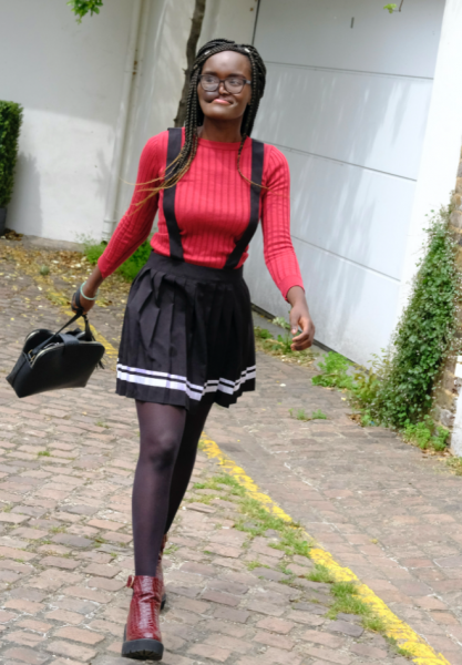 A young black woman strides confidently down the street. She is wears a red top and black skirt