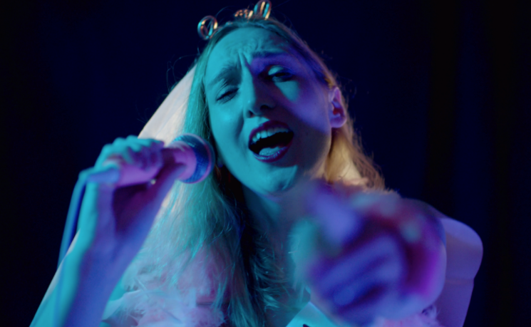A white woman sings into a microphone and wears a tiara and wedding veil