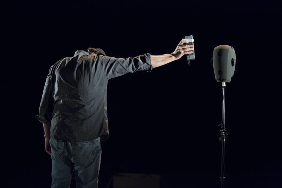 Simon McBurney, dramatically lit against a black background, holding a tape recorder out to a binaural microphone which looks like a high-tech mannequin head