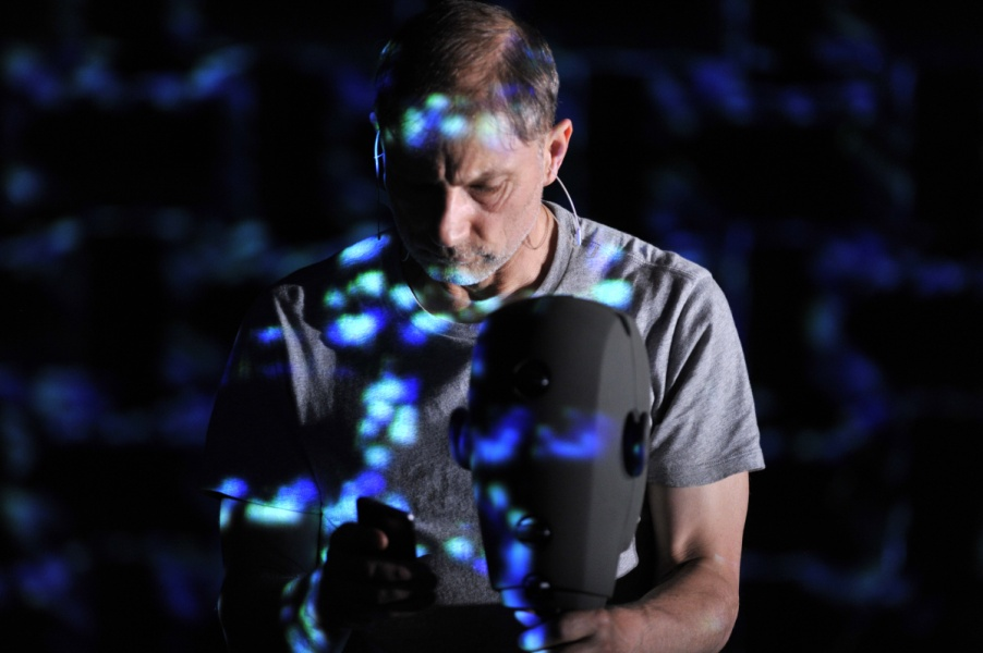 Simon McBurney, speckled with blue light looking down at his phone in front of a binaural microphone