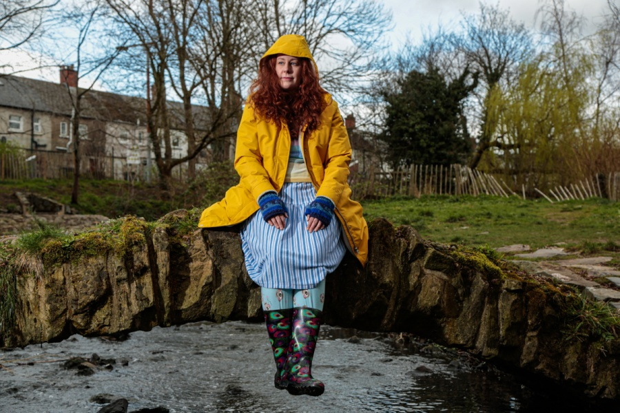 A woman with red hair wears a bright yellow southwester and hat. She sits on a bridge over a stream