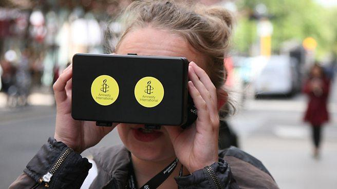 Lady using VR headset with two yellow amnesty international stickers on it